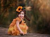 دختر بچه شاد با گل سر خوشگل
