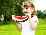 دختر بچه خندان در حال خوردن هندوانه