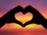 دو دست به شکل قلب در غروب